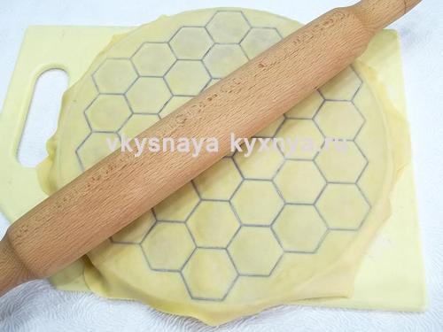 Раскатанный скалкой пласт теста на форме для пельменей